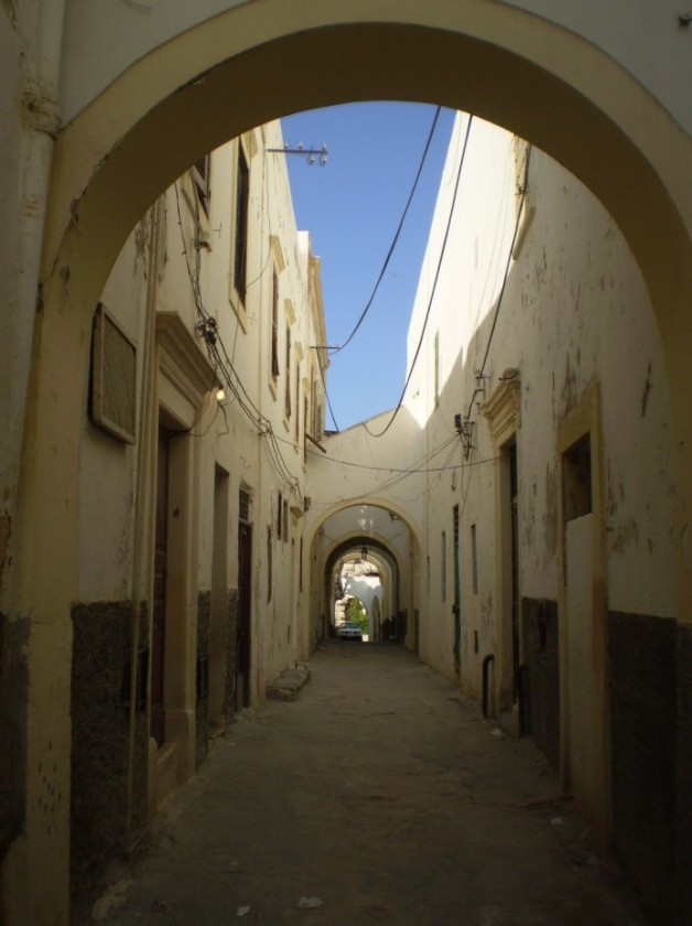 A narrow street running through a residential area in Tripoli, Libya.